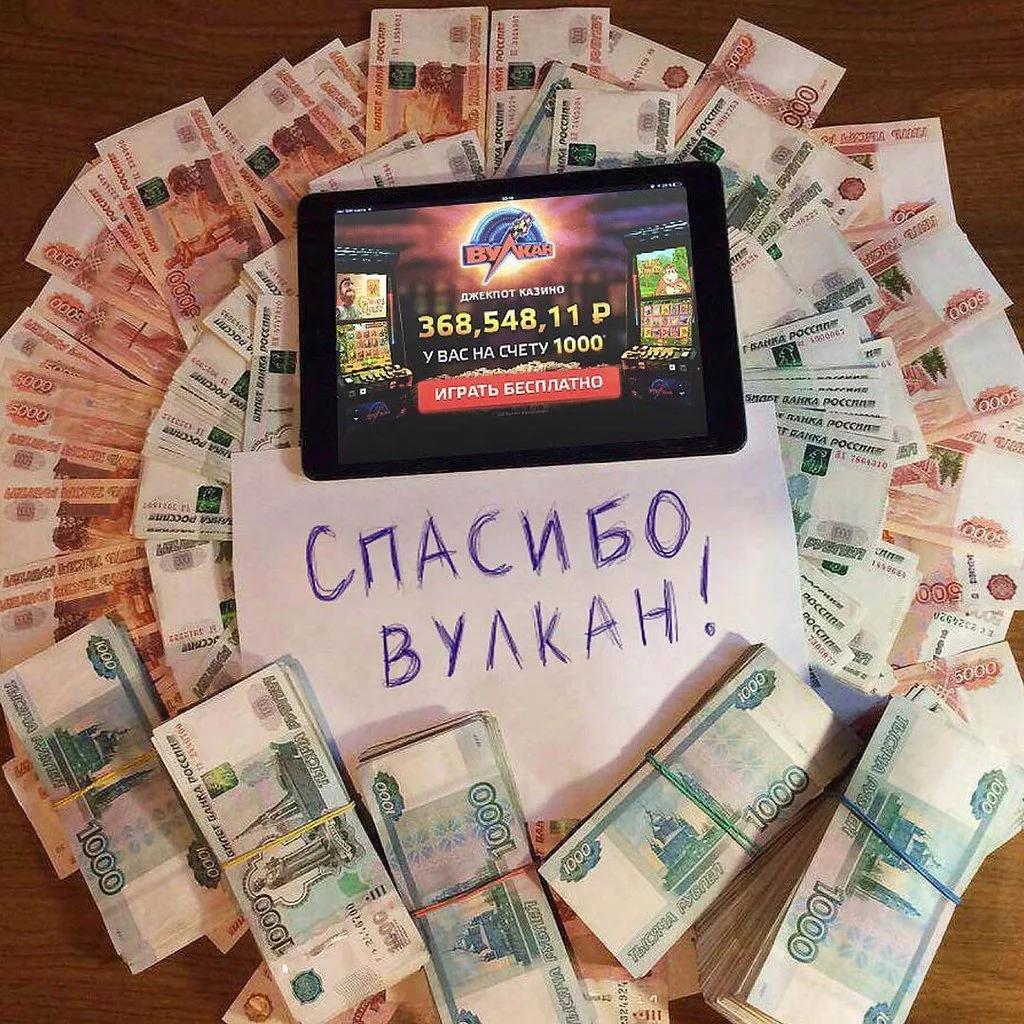 """Планшет, вокруг которого разложены пачки денег. На планшете лого казино. В центре лист бумаги с надписью: """"Спасибо вулкан!"""""""
